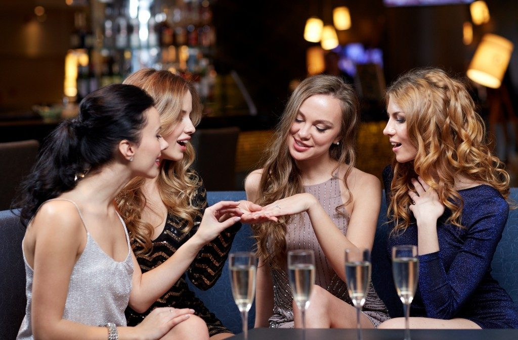 happy woman showing engagement ring to her friends
