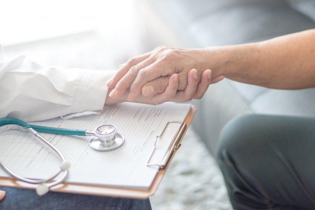 Elder's hand holding doctor's hand