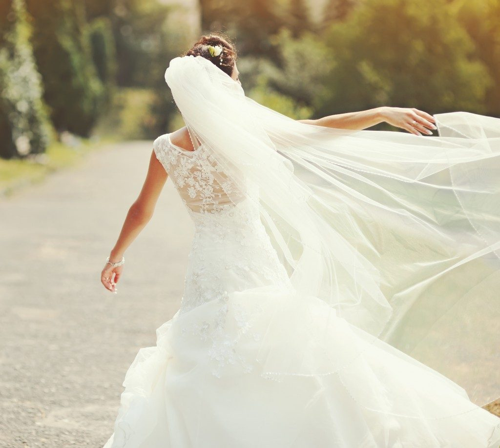 Happy bride spinning around with veil