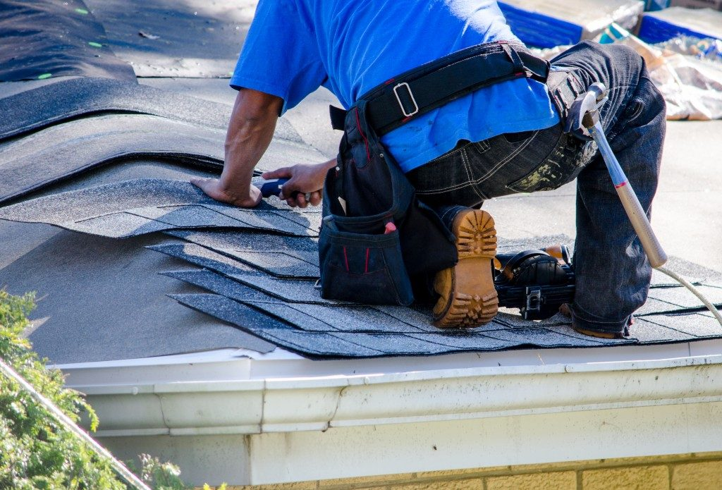 Worker replacing shingles