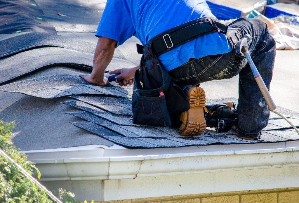 Worker replacing shingles