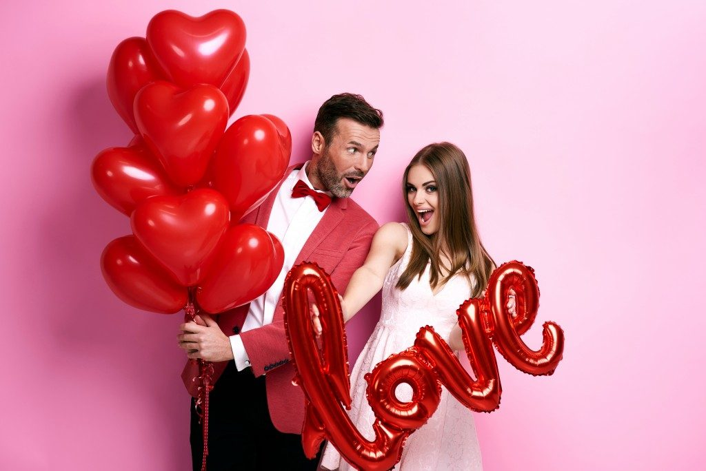 Happy couple with hearts and love balloons