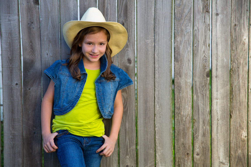 Children girl as kid cowboy girl cowgirl posing on wooden fence far west style