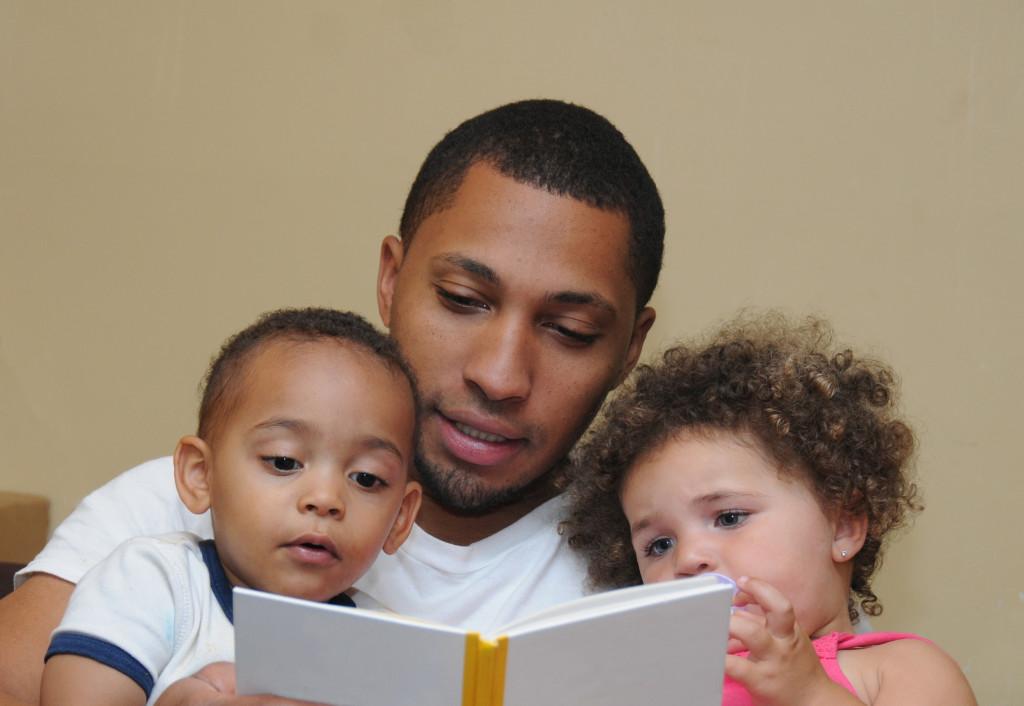 man reading to his children